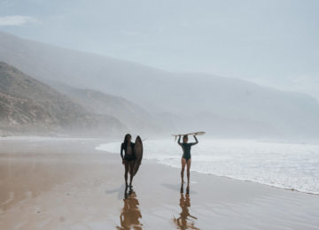 Two people with surfboards walk on the beach