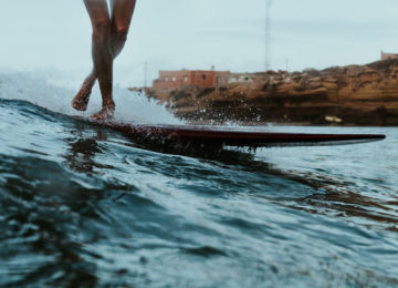 Surfer rides the wave with longboard