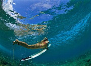 Surferin mit duck dive in glasklarem Wasser