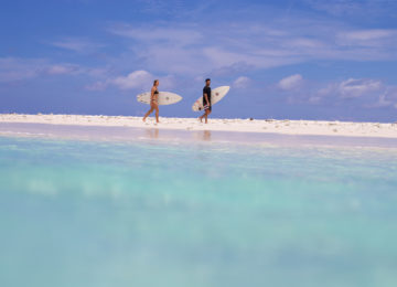 Surfer spazieren am Strand entlang