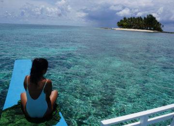 Gast blickt vom Boot aufs Korallenriff