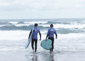 Surfers run into the waves with a board