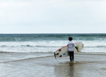 Surfer runs into the waves with board
