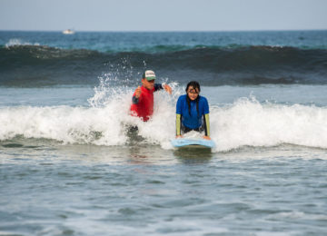 Beginner surfer with coach at pop-up