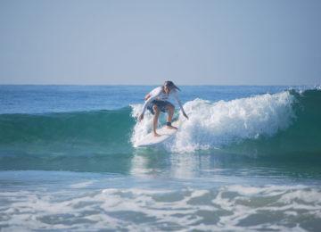 Surfer surfs green wave