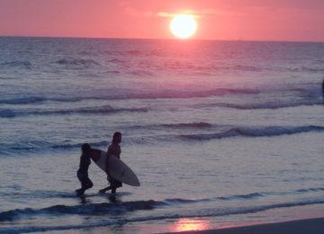 Surfer steigt bei Sonnenuntergang aus Wasser
