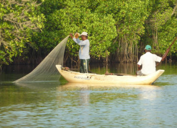 Fishermen on the river with canoe and net