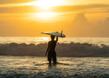 Surfer blickt im Meer auf Sonnenuntergang
