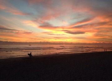 Sonnenuntergang mit Surfer am Strand