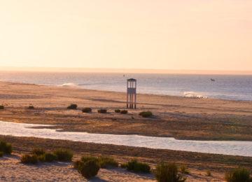 Ein Turm überragt das Flachland und das Meer mit Wellen