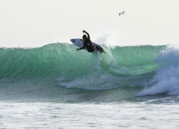 Ein Surfer macht auf der Welle ein Manöver
