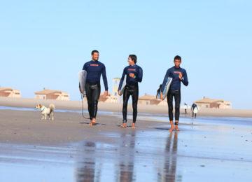 Drei Surfer laufen am Strand entlang