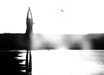 Eine Frau posiert in einer Yogaposition am Strand