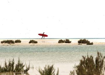 Ein Surfer auf dem Weg ins Wasser