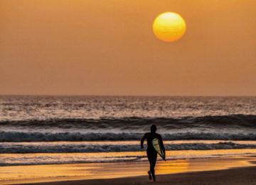 Ein Surfer rennt bei Abendsonne am Strand in Richtung Wasser