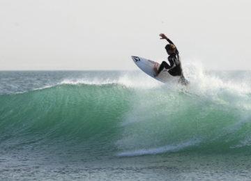 Ein Surfer im Neoprenanzug reitet eine Welle