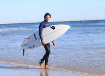Ein Surfer lacht in die Kamera und hält sein Brett unterm Arm
