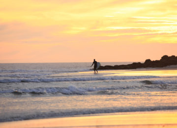 A surfer runs into the water in the evening sun