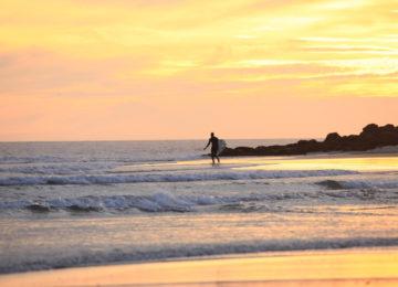 Ein Surfer läuft ins Wasser bei Abendsonne