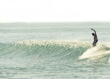 A surfer practises his skills on the board and the wave