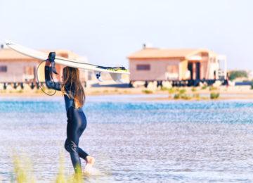 Eine Surferin läuft im Wasser und trägt ihr Surfbrett auf dem Kopf