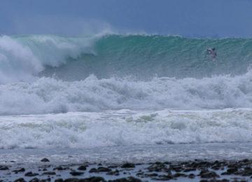 Surfer paddles over left wave