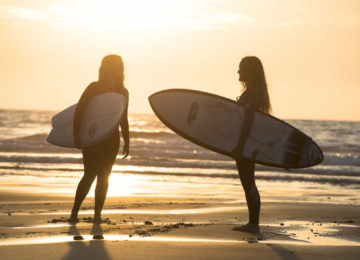 Zwei Surferinnen beim Sonnenuntergang
