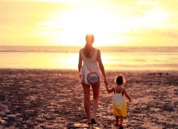 Mama mit Kind laufen am Strand