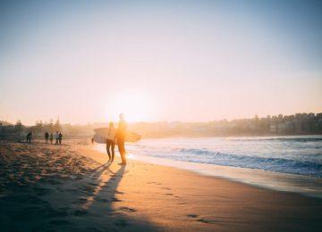 Zwei Surfer kommen vom surfen zurück an den Strand