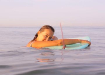 surfer lady with surfboard in water