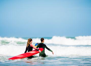 Surfschülerin und Coach im Wasser