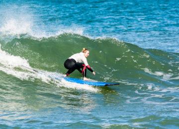 Surfschülerin auf grüner Welle